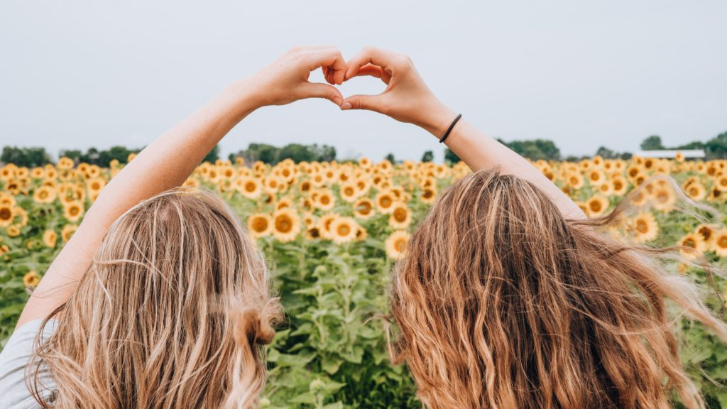 Tow friends creating a heart with their hands as they stand and look at a field of sunflowers.  Sunflowers that remind us to live with purpose.