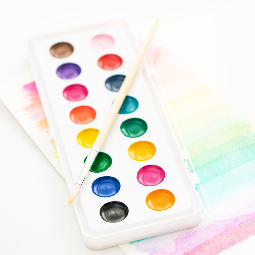 A set of watercolor paints and paintbrushes sitting on top of some rainbow colored fancy artwork.