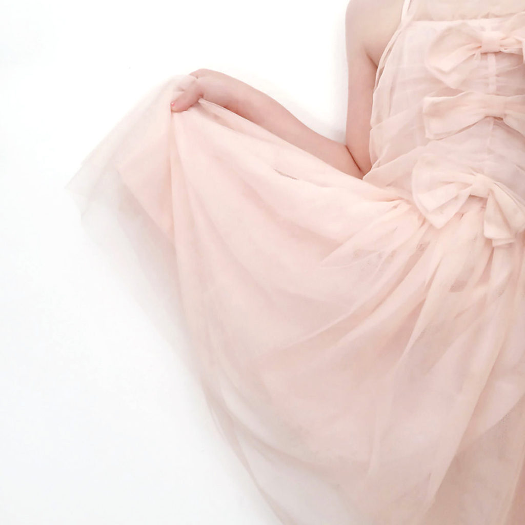 A young girl in a fancy pink dress, holding her skirt up like a princess with one hand.