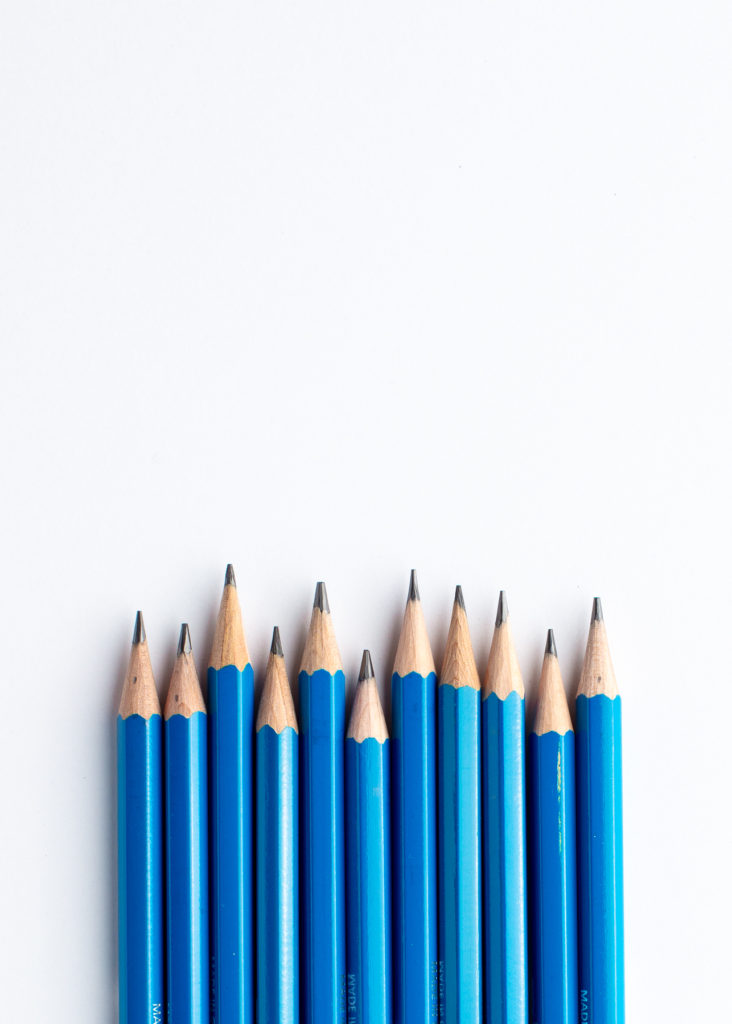 Blue school pencils, sharpened and lined up neatly.