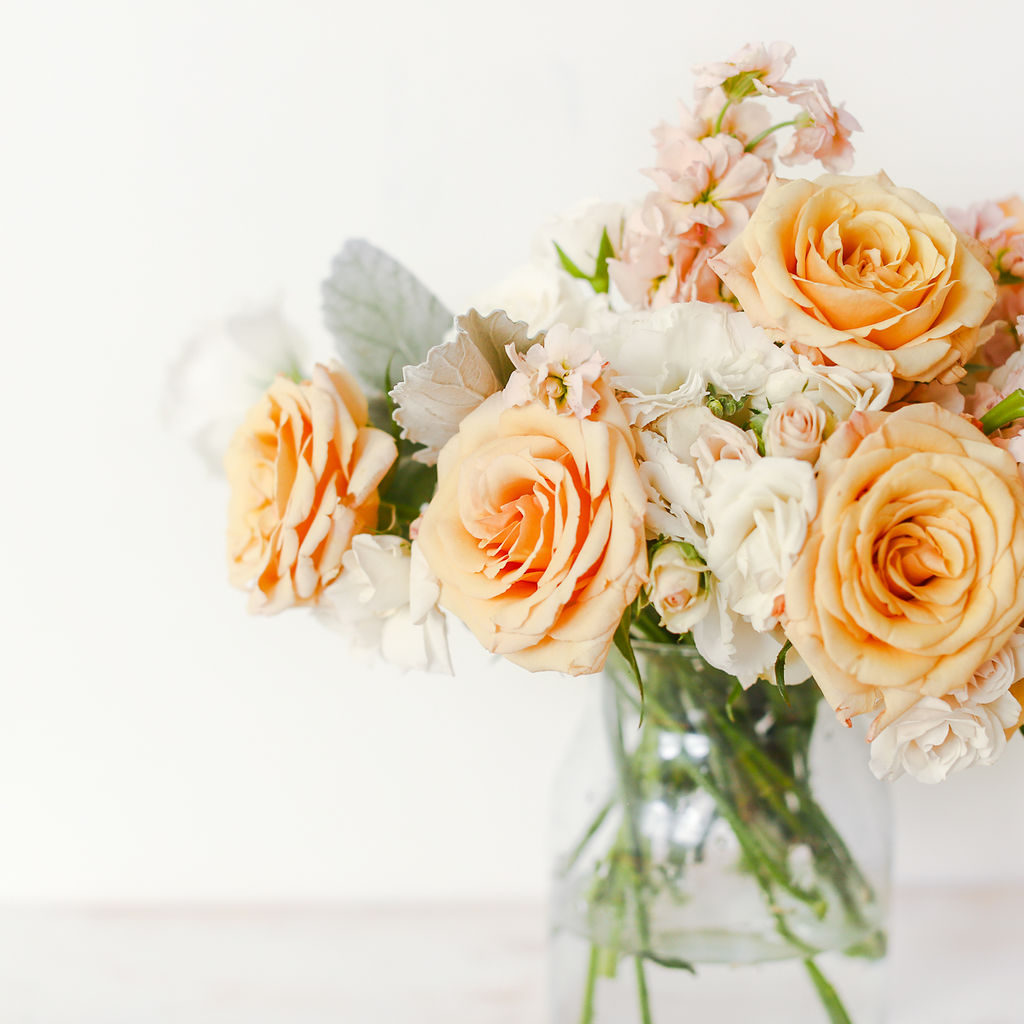 A clear vase of peach and white roses sitting on a cream colored table.