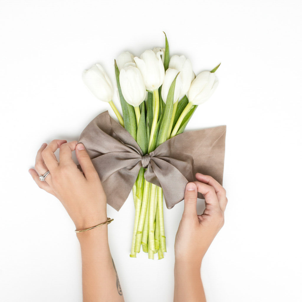 A group of white tulips being tied together with a gray satin ribbon.