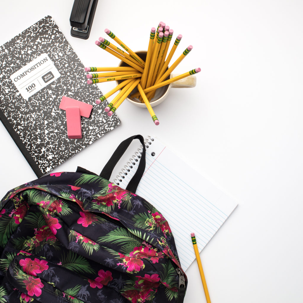 A school backpack, notebooks, yellow pencils in a cup, and pink erasers on a white background.