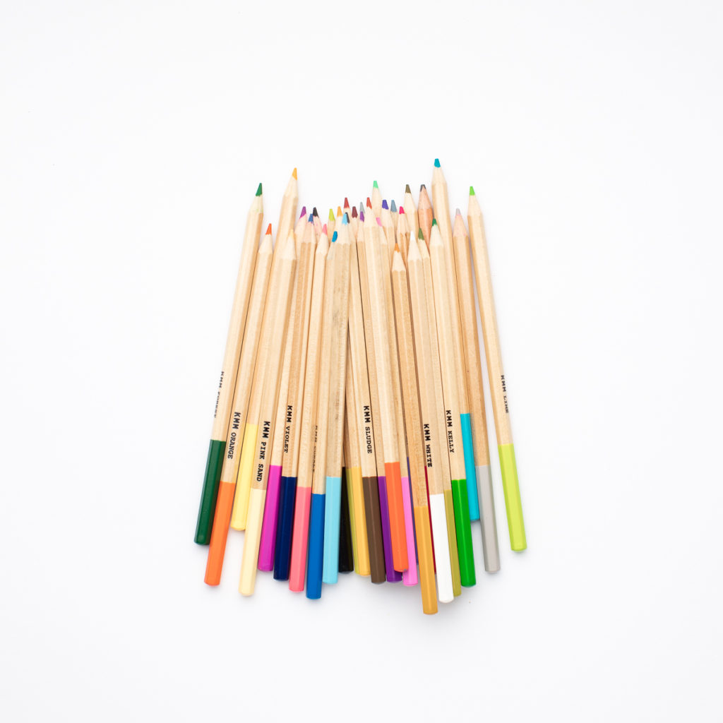 A handful of colored pencils laying on a white table - colored pencils that are extremely helpful in homeschooling!