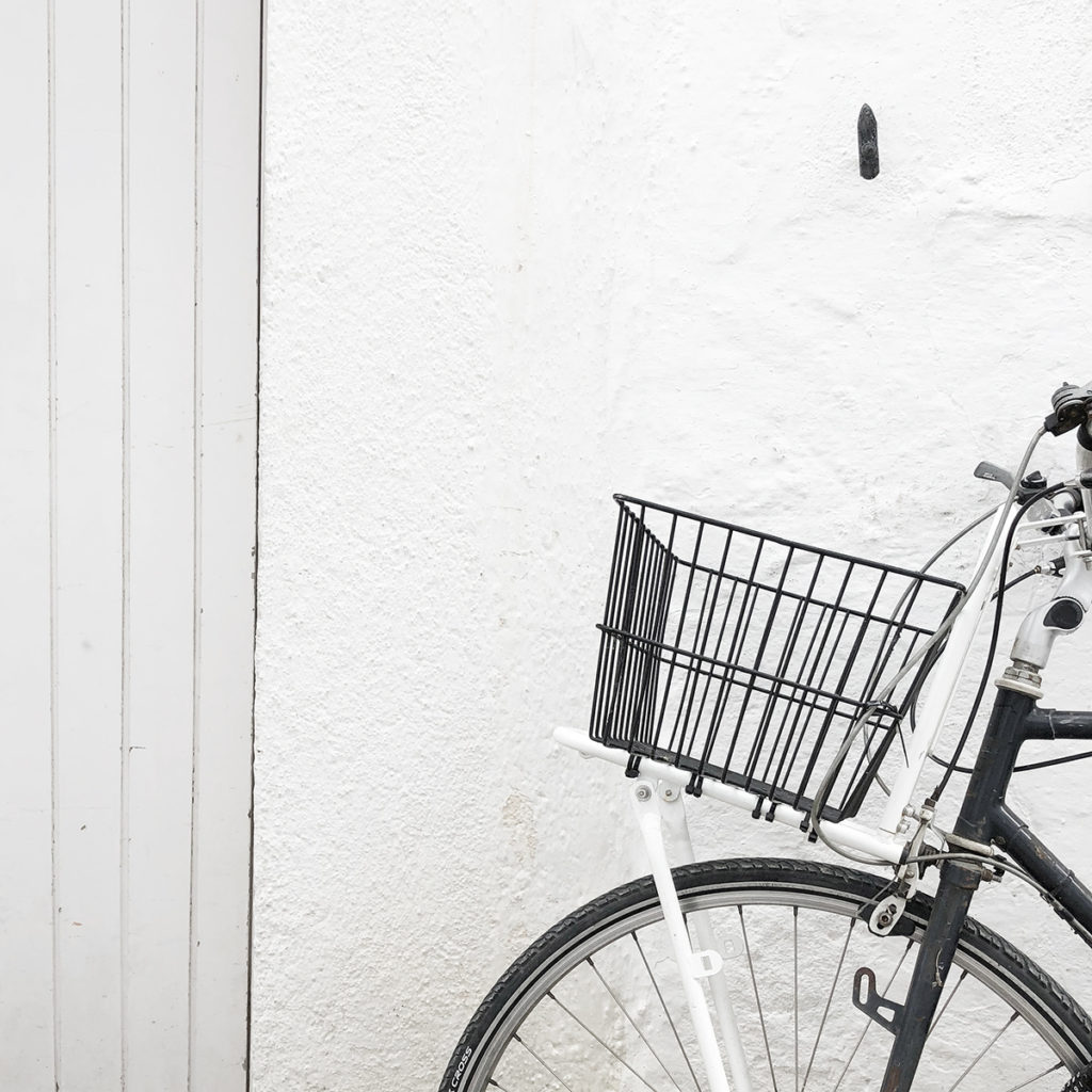 A bicycle with a wire basket leaning against a white wall.