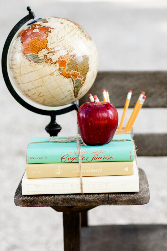 A globe, red apple, yellow pencils, and books tied with twine sitting on a wooden desk ready for a school day.
