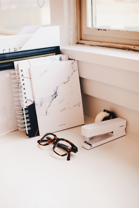 Notebooks sitting on a desk below a window along with some glasses and a stapler.