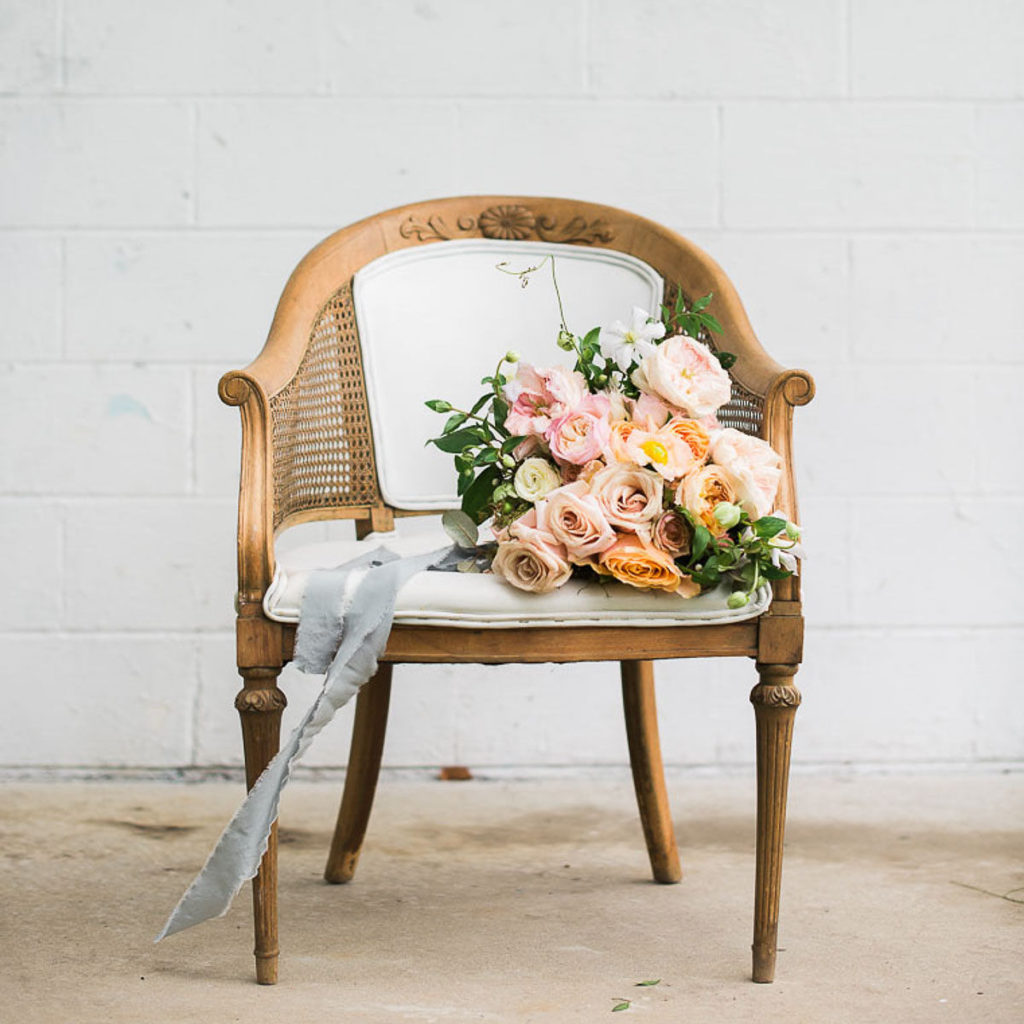 A bouquet of flowers tied with a long, trailing ribbon sitting on an antique armchair to remind you to pause and learn how to control your emotions.