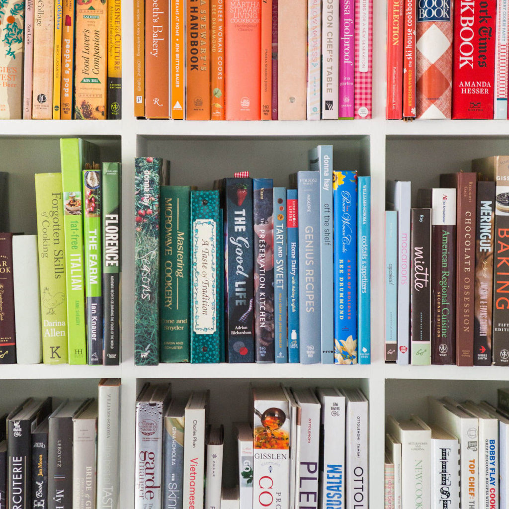 Colorful books arranged on a white bookshelf to look like a rainbow.