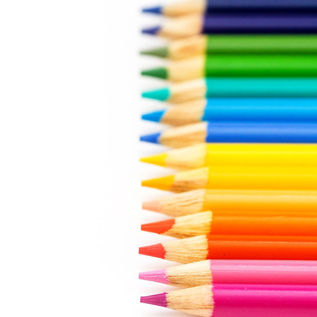 Sharpened colored pencils, like you would use in homeschooling, all lined up to create a rainbow.
