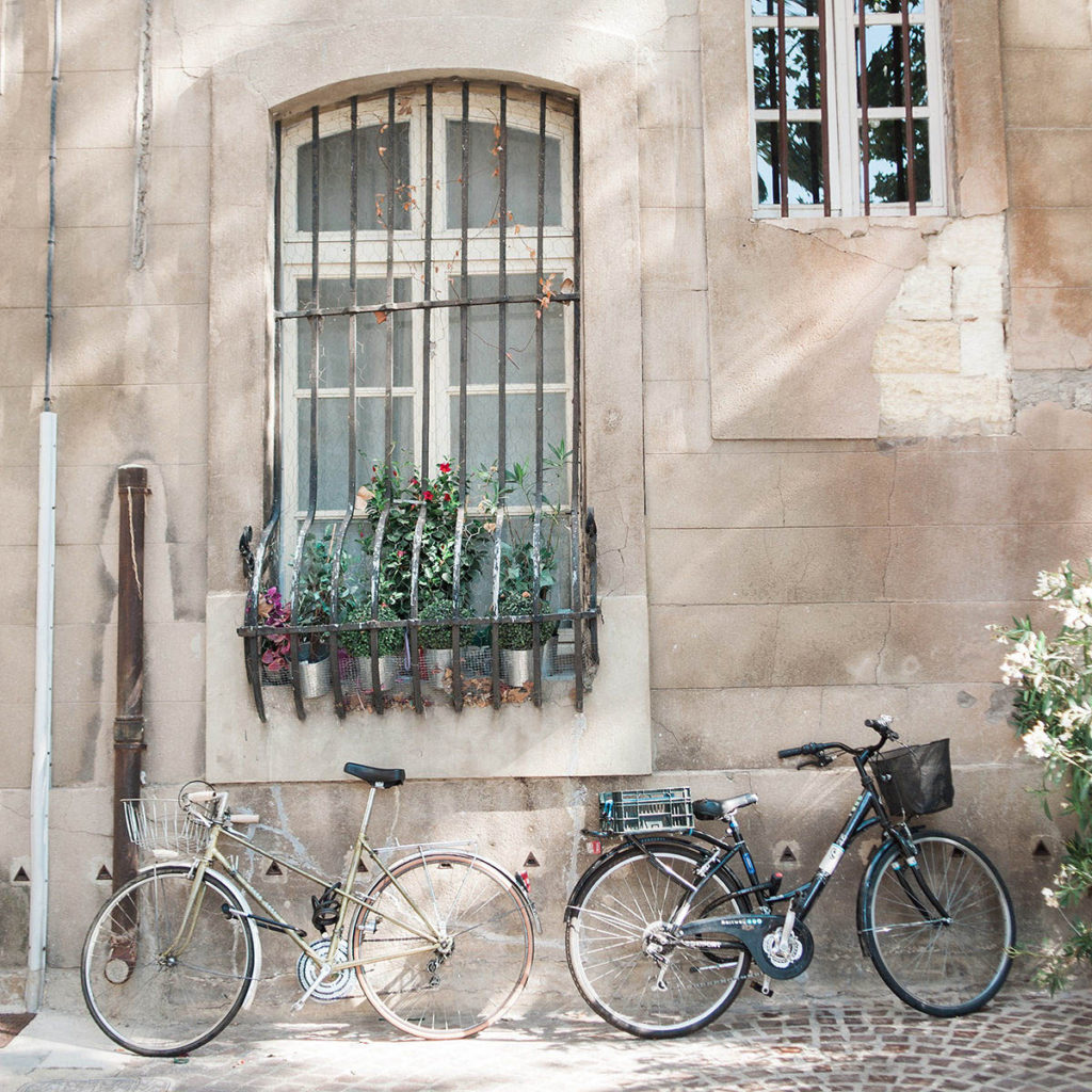 Two bicycles parked against a wall with windows and flowers growing in window boxes.