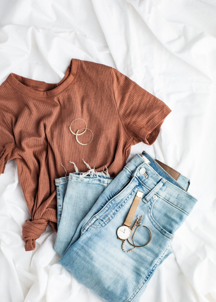 Layout of jeans, a brown shirt, a watch, and earrings to show what clothes needs to be packed.