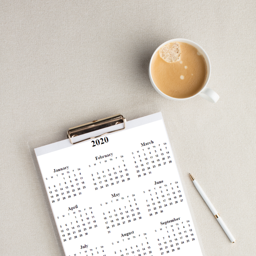 A 2020 yearly calendar on a clipboard next to a cup of coffee.