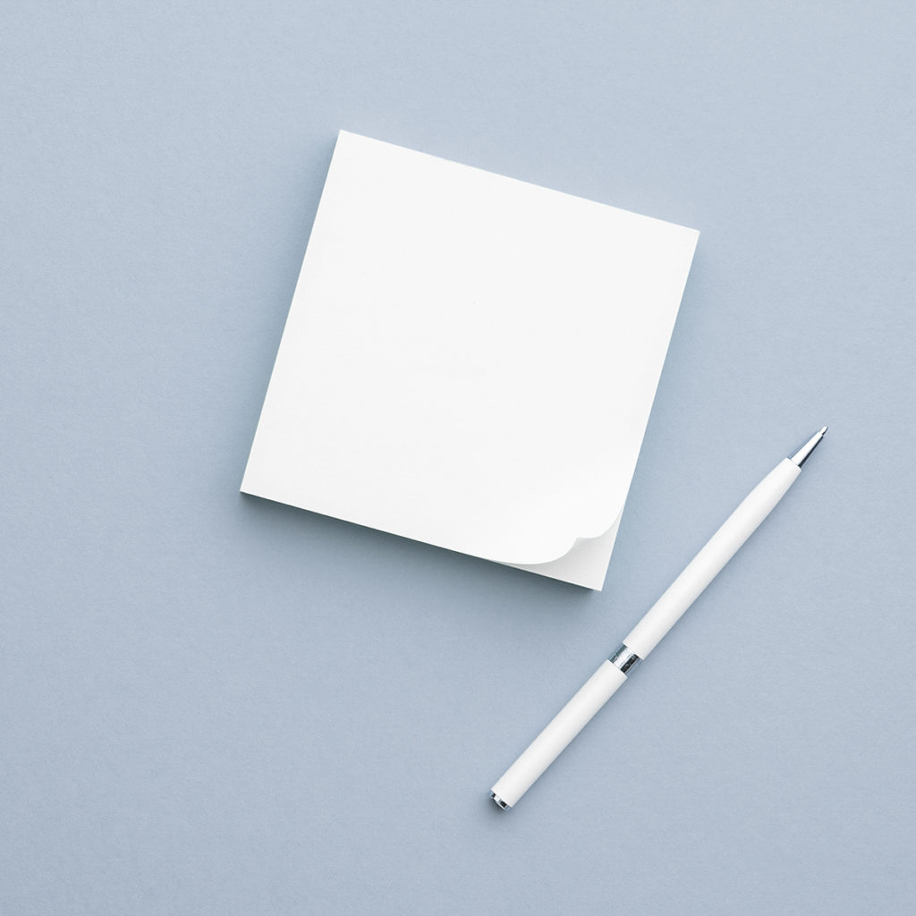 A pack of post-it notes and a pen to use while sorting your cluttered piles of paper.