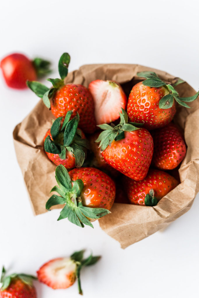 Strawberries spilling out of a brown paper bag.