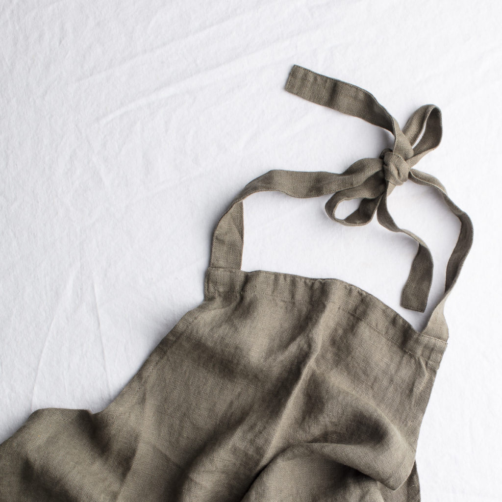 An olive green apron laid out flat.