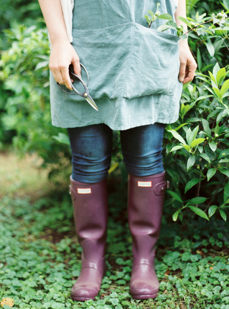 A person standing wearing a garden apron and garden boots while holding pruning sheers.  They are ready to bring change to their garden.
