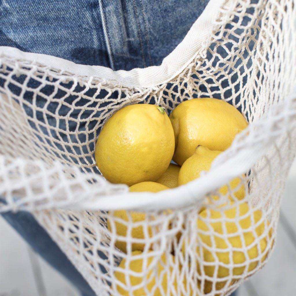 A person in blue jeans holding a net grocery bag of lemons.