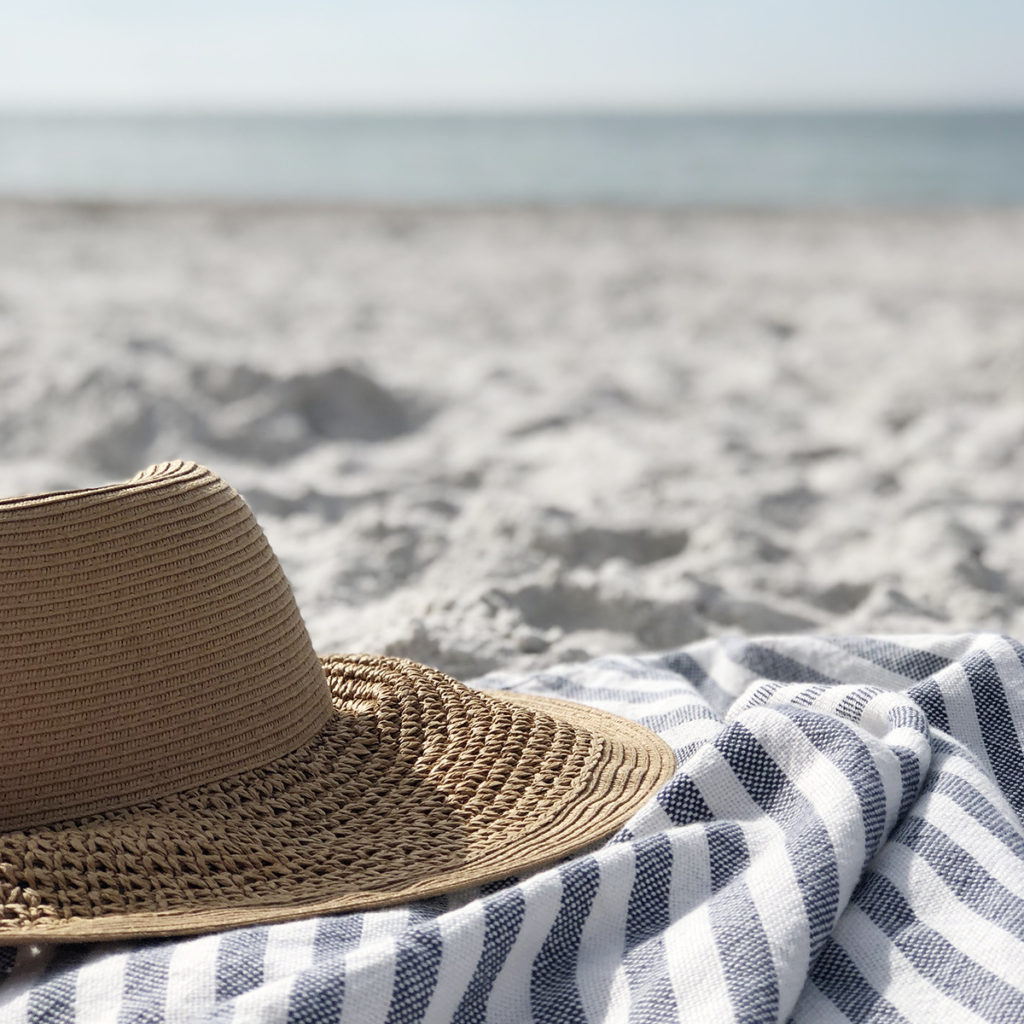 A beach hat sitting on a striped towel on the sand with the water in the distance.