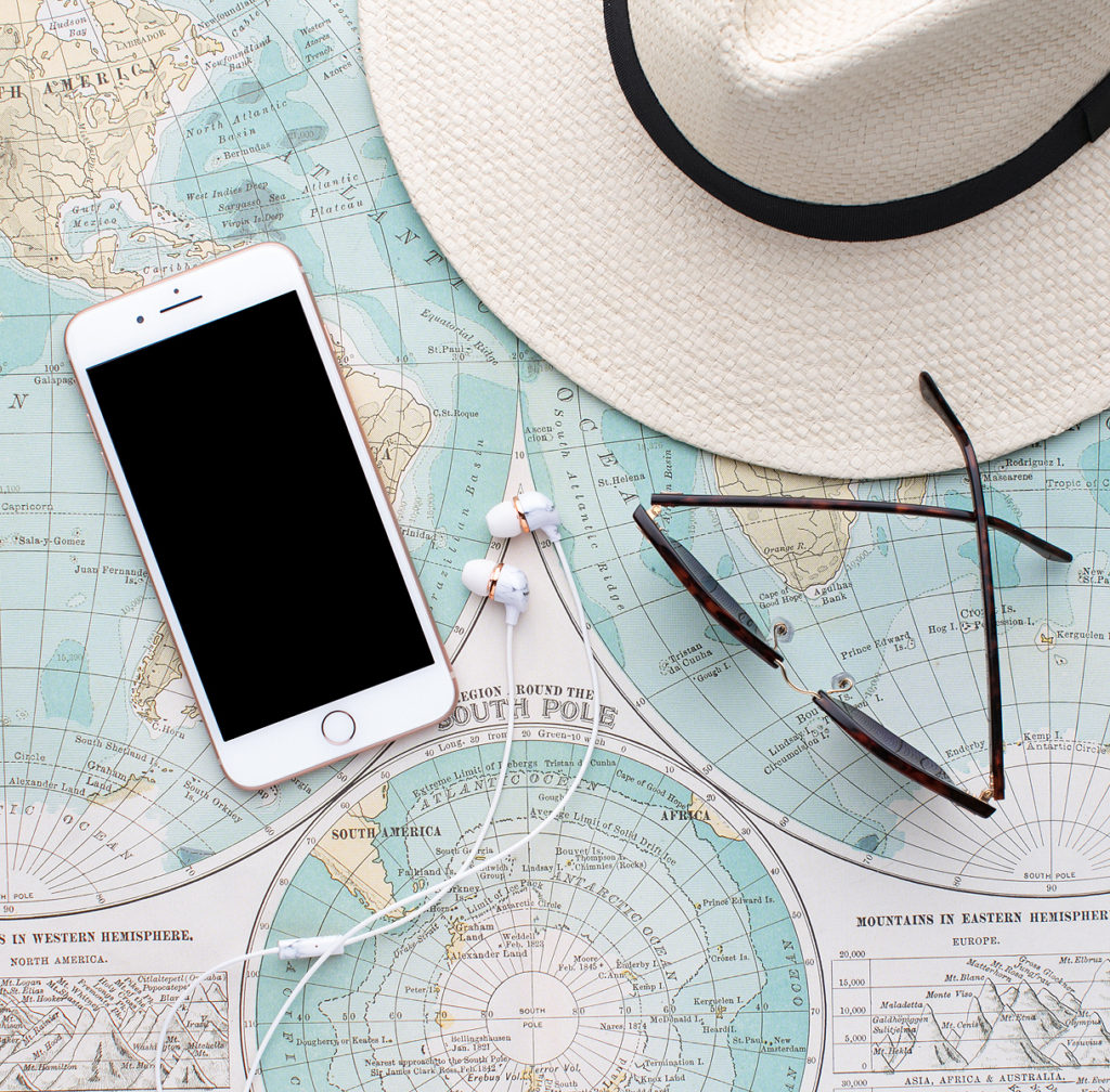 A phone, sun hat, and sunglasses sitting on a paper map.