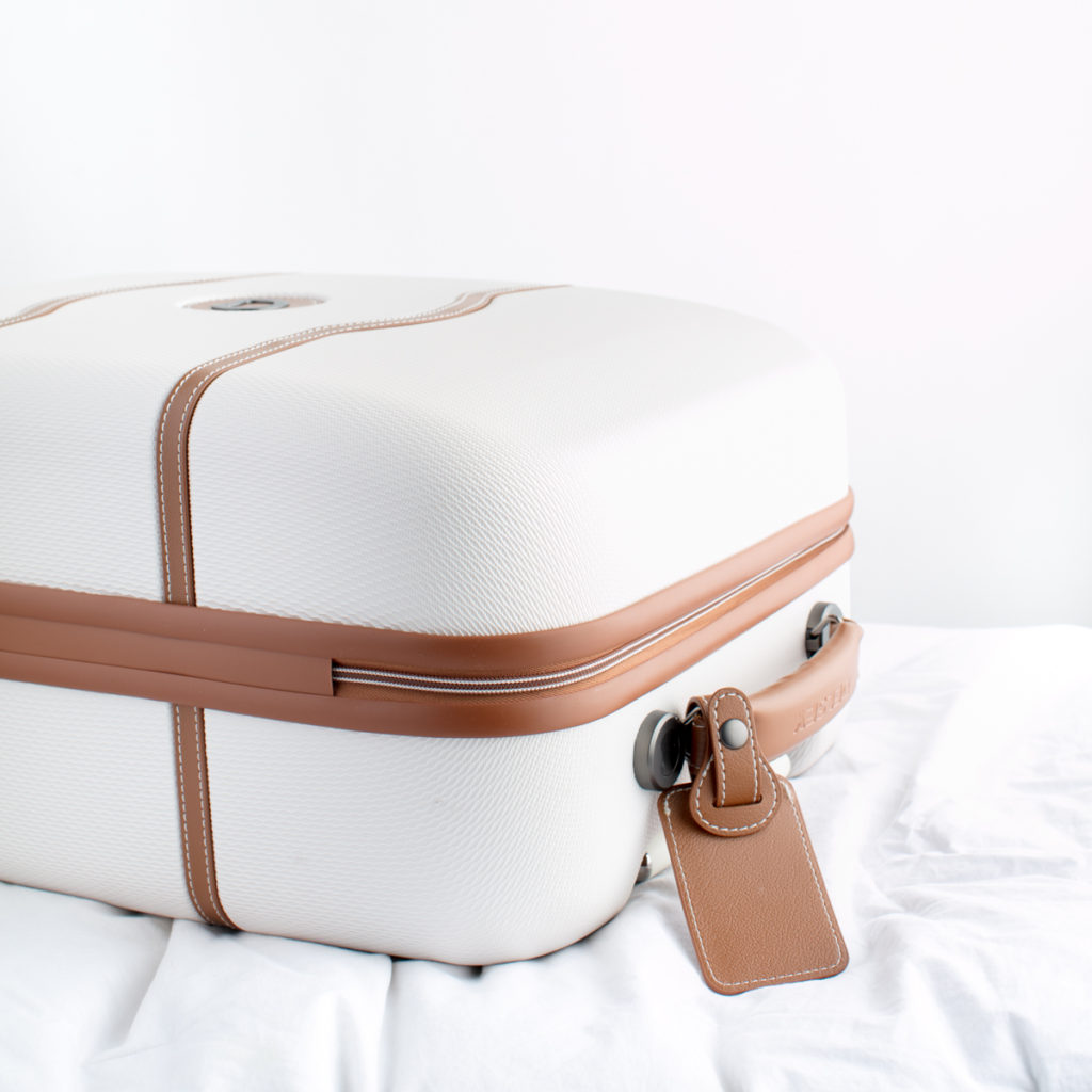 A white and brown suitcase packed and ready to go on a road trip.