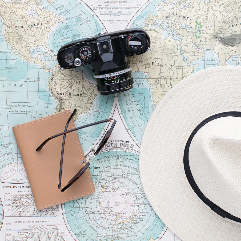 A sun hat, notebook, sunglasses, and a camera sitting on a paper map.
