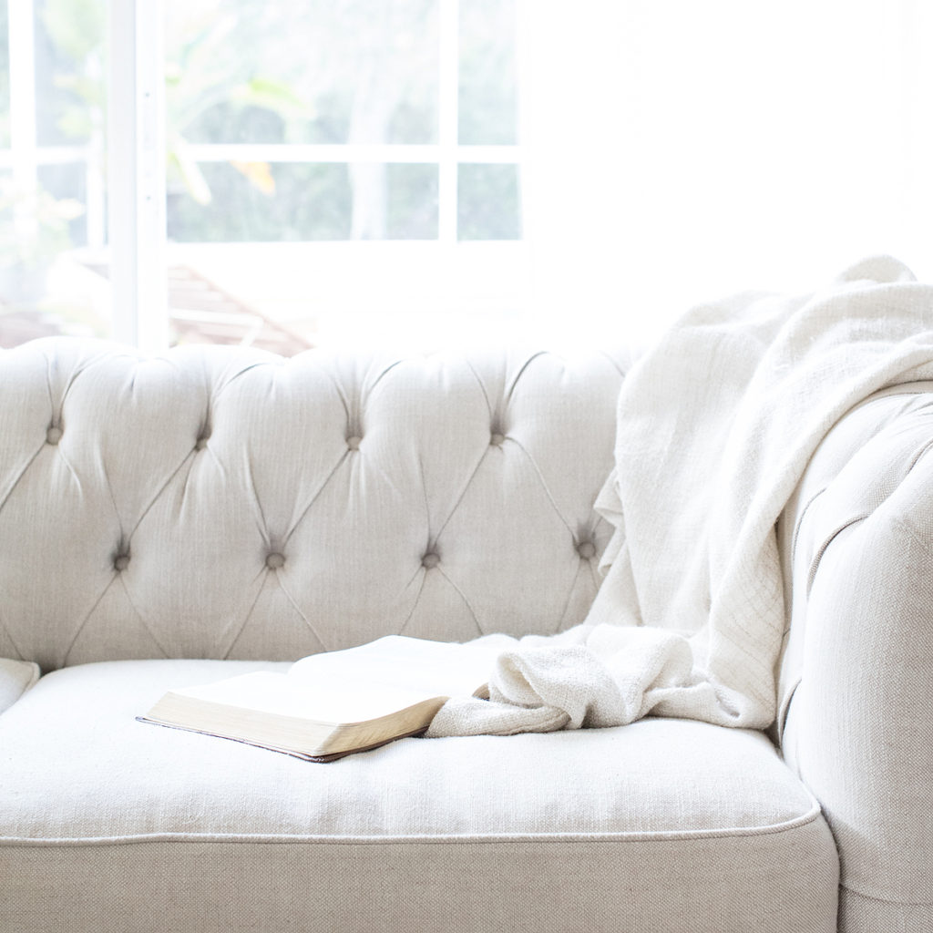 Sunlight streaming onto a light gray couch, inviting you to a conversation.