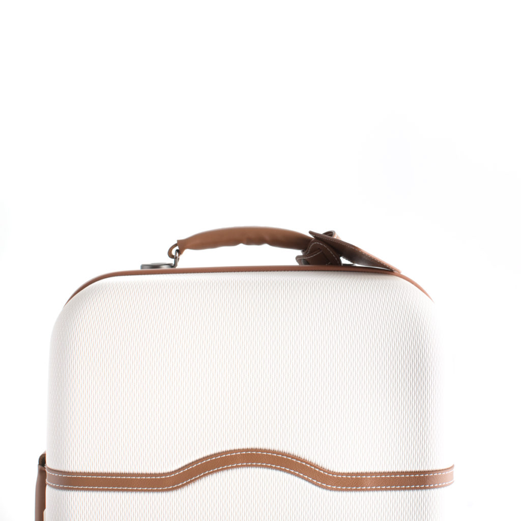 A cream and brown suitcase packed and ready to go on a road trip.