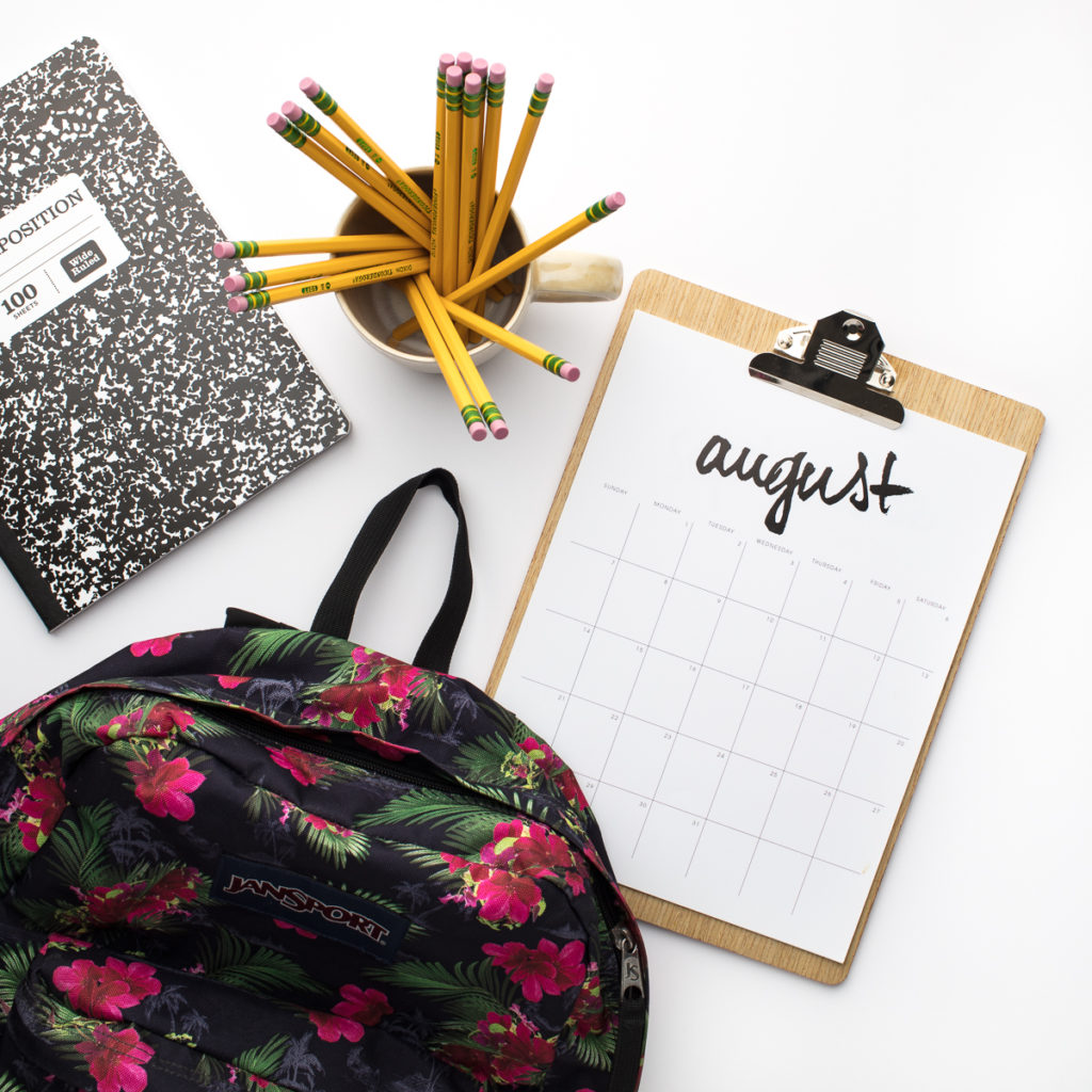 Picture of a calendar on a clipboard complete with school backpack, pencils and notebook.