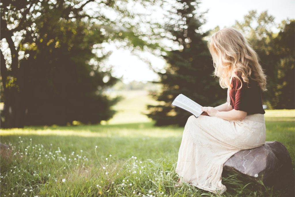 A young girl reading in a meadow with the sunlight streaming down around her.