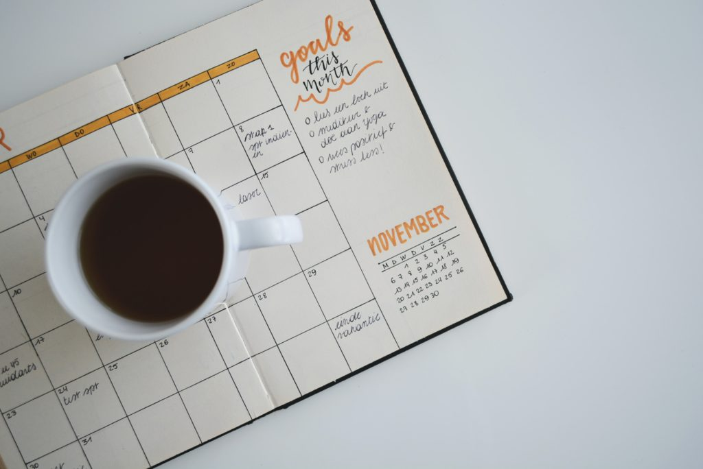 A cup of coffee sitting on a monthly calendar.