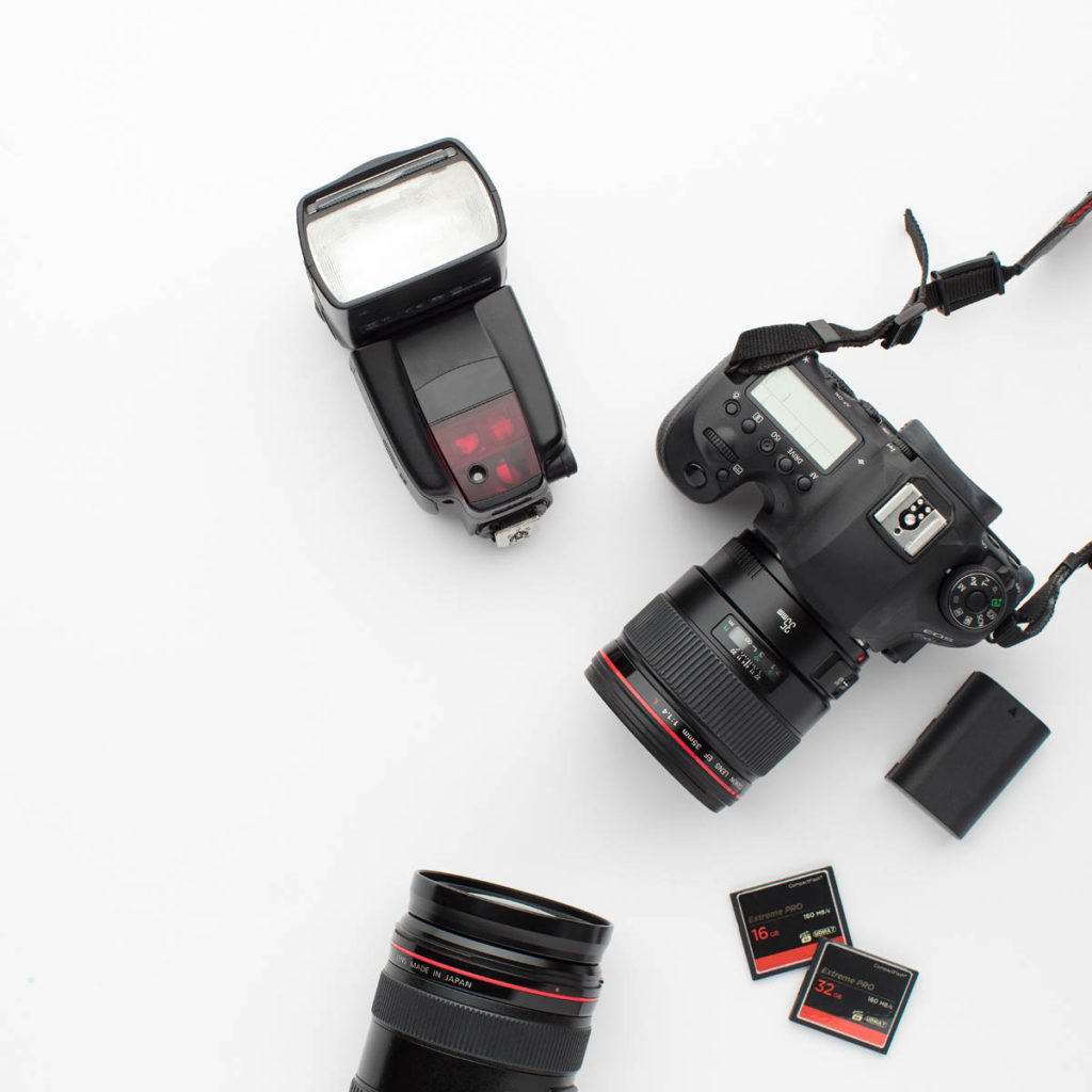 A camera sitting next to the external flash, memory cards, and extra telephoto lens.