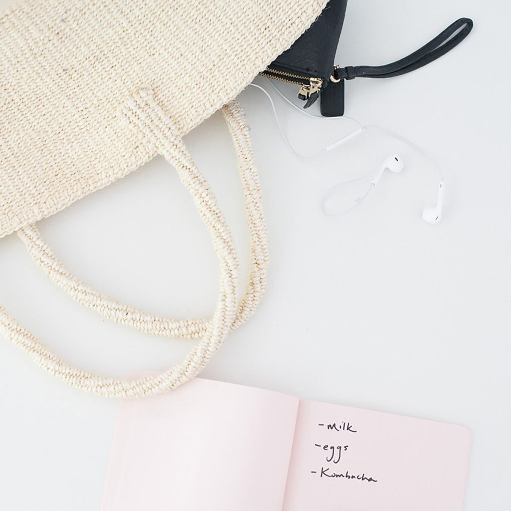 A cream colored bag complete with notebook and earbuds, ready for a road trip.