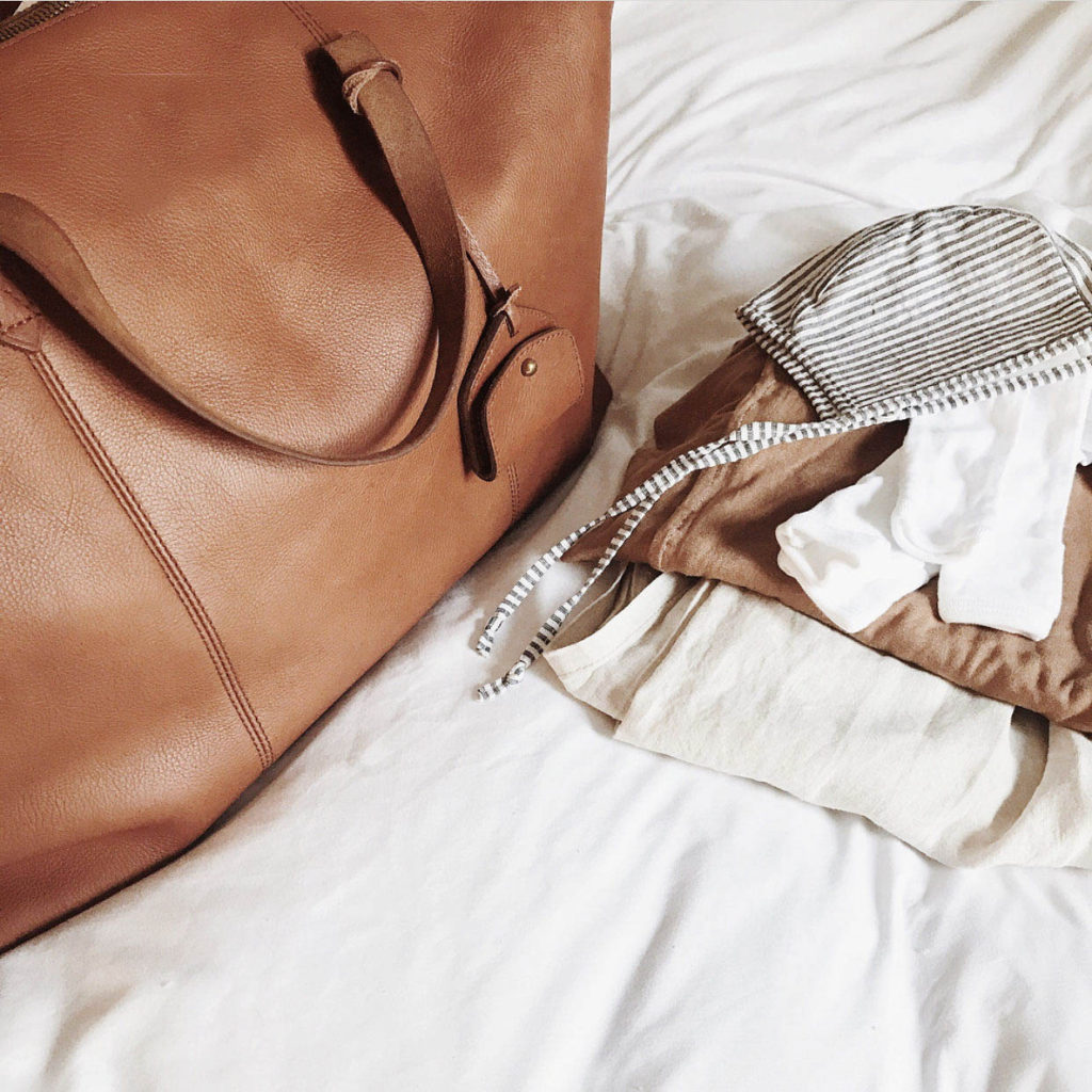A leather bag, partially packed, with clothes folded and sitting next to it.