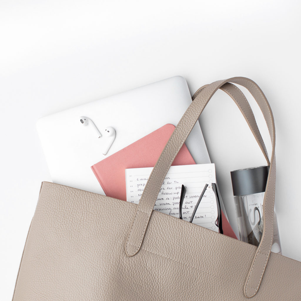 A leather bag with a laptop, notebook, pair of glasses, and earbuds inside.