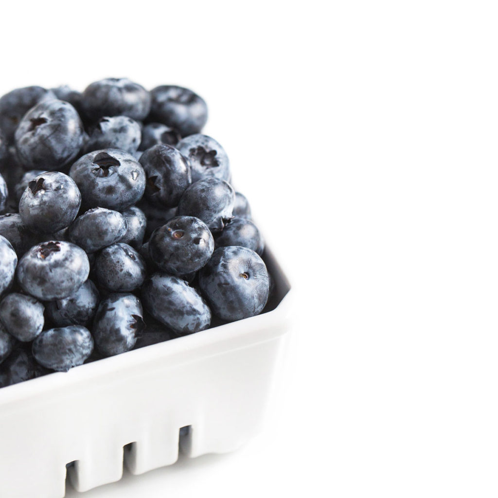 A close picture of a carton of blueberries.