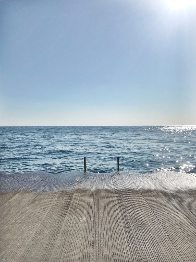 A wooden pier leading over the edge of the water.  When you start to understand imposter syndrome, you start to feel like you're getting above it.