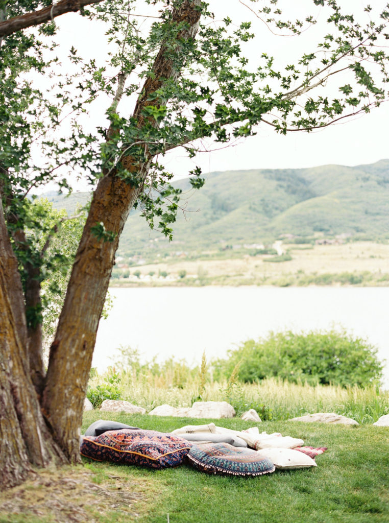 A tree reaching over a reading spot by a river.  A perfect spot to enjoy summer.