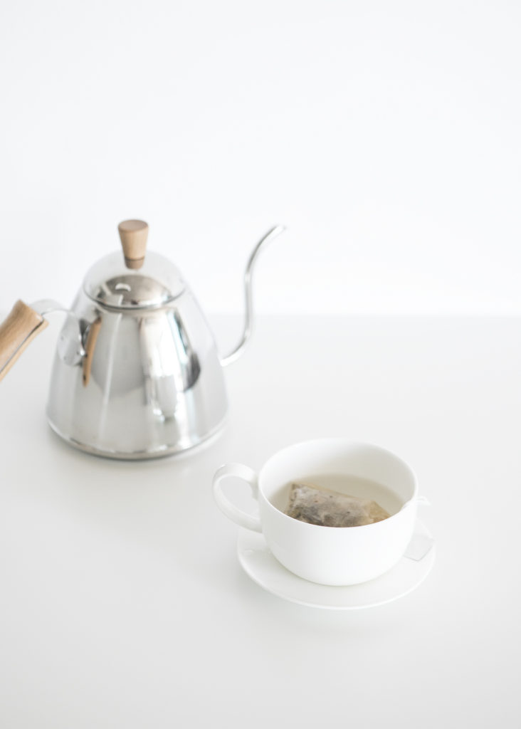 A silver teapot sitting next to a white tea cup filled with tea.  A reminder to enjoy the simple things in summer.