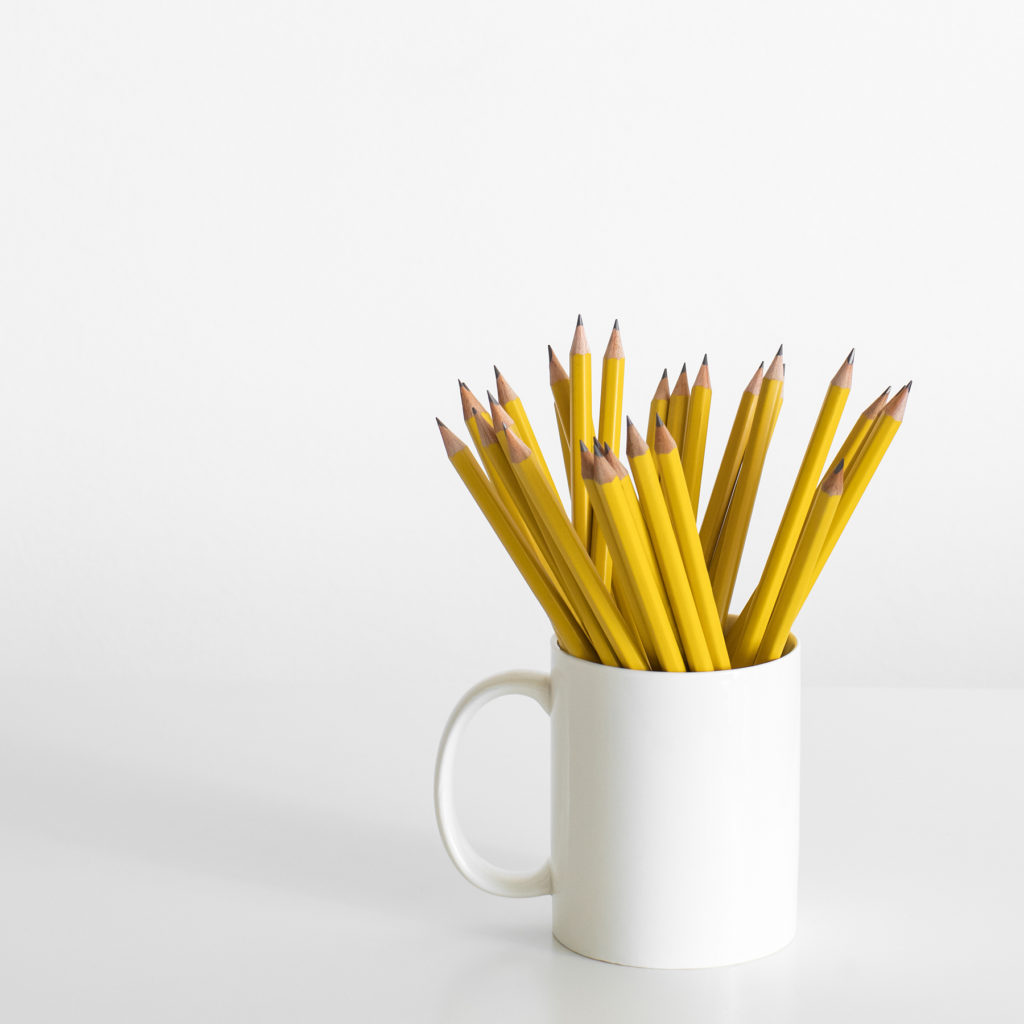 A white mug filled with yellow pencils that you can use to fill out your curriculum grid.