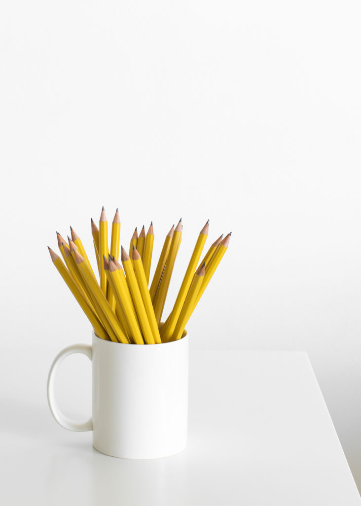 A while mug of yellow pencils sitting on a white table.