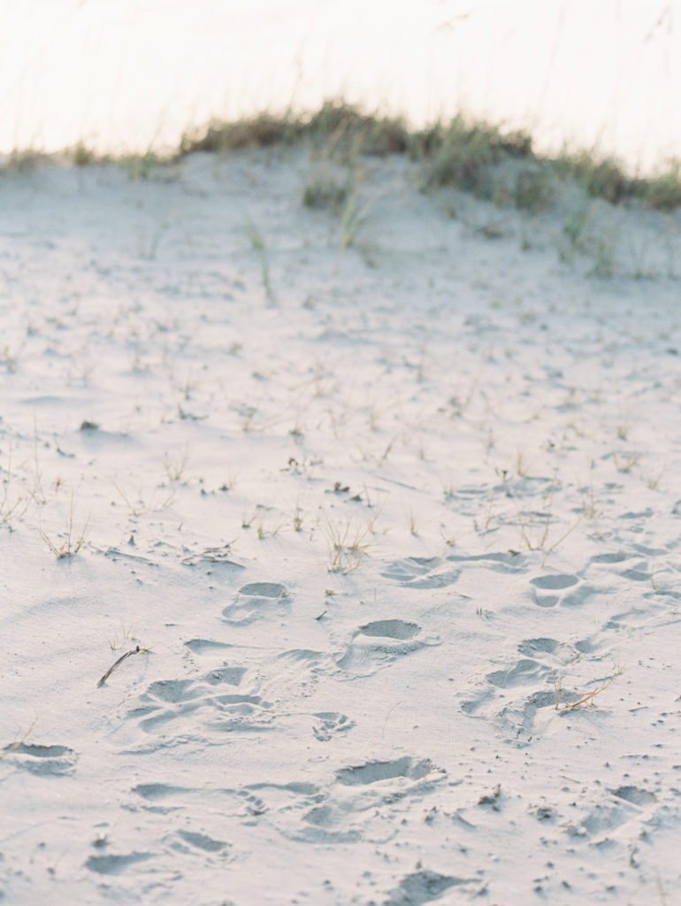 A sandy beach with footprints leading up to the beach grass in the distance.