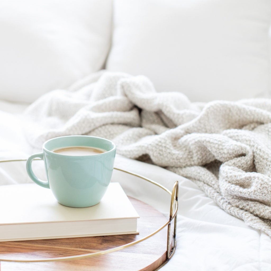 A cup of coffee sitting on a side table next to a couch, inviting a conversation.