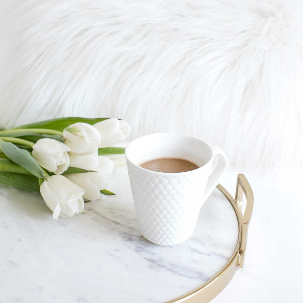 A white mug filled with coffee next to white tulips sitting on a bedside table.