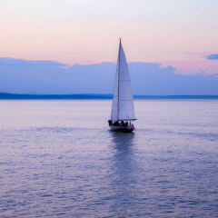 A sailboat gently gliding on the calm waters before a beautiful sunset.
