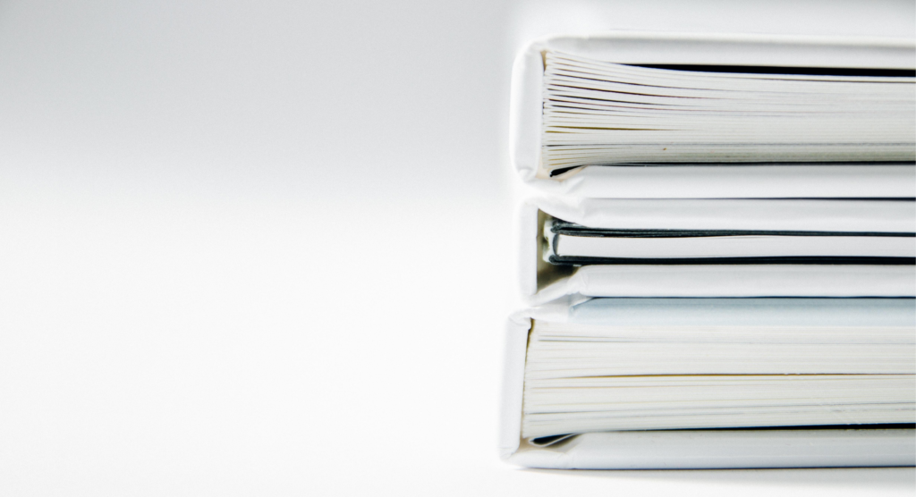 A picture of 3 white binders stacked up.  Binders are one of the best tools for organizing your homeschooling space.