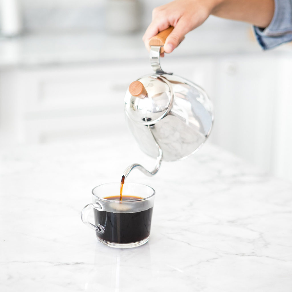 Black coffee pouring out of a silver coffeepot into a glass mug on a white marble counter.