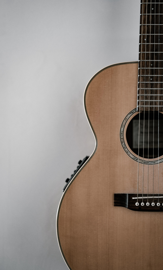 A polished guitar standing against a white wall.