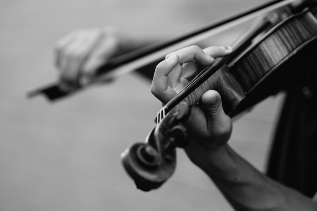 A black and white photo of a violin being played.