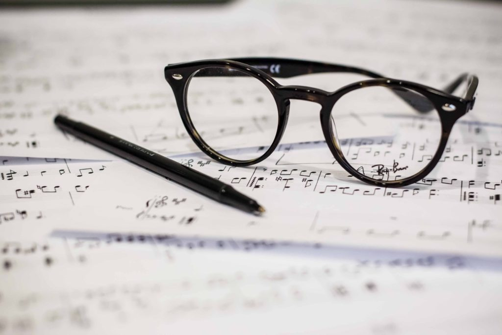A pair of black rimmed glasses sitting on scattered pages of sheet music.